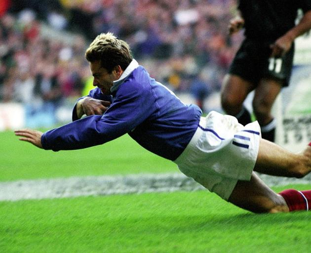 French winger Christophe Dominici scores against the All Blacks in the 1999 Rugby World Cup...