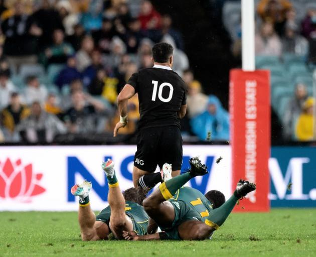 Richie Mo'unga breaks the tackles of Wallabies Michael Hooper and Marika Koroibete in Sydney last...