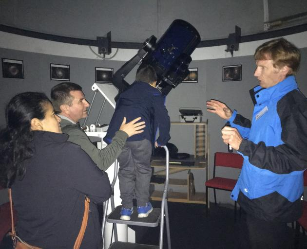 Oxford Observatory volunteer James Moffat (right) helps a family view the cosmos through the 10...