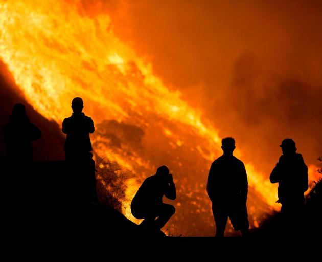 Residents are silhouetted as they watch the Blue Ridge Fire burning in Yorba Linda, California....