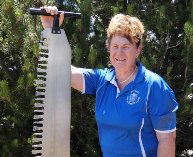 Mrs Taylor shows off the single-handed saw, which is but one of the tools she uses as she...