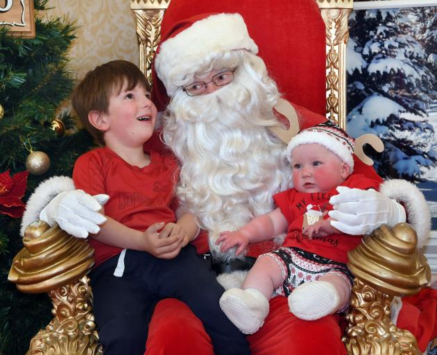 Lucas Thompson gives Santa his wish list in Dunedin's Meridian Mall yesterday, and lets his baby...