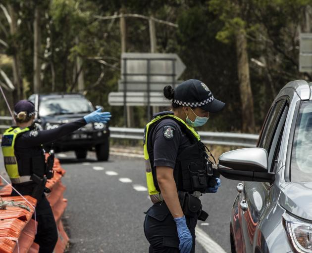 Police check for entry permits to Victoria at a border checkpoint last month. PHOTO GETTY IMAGES