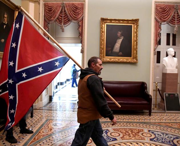 A supporter of President Donald Trump carries a Confederate battle flag on the second floor of...