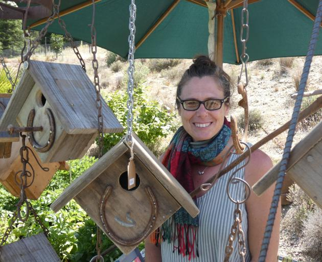 Ettrick artist Vauna Turner stands among some of the bird houses she has crafted from fruit...