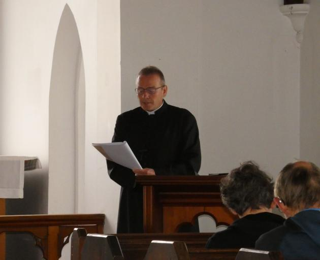 Anglican Bishop of Dunedin the Right Rev Dr Steven Benford reads the paperwork to secularise St...