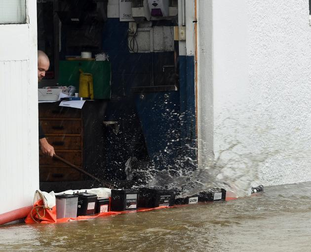 A Normans Auto Electrical employee sweeps water out of the building during yesterday's flooding...