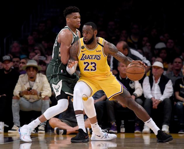 Los Angeles Lakers forward LeBron James (with ball) posts up against Milwaukee Bucks forward...