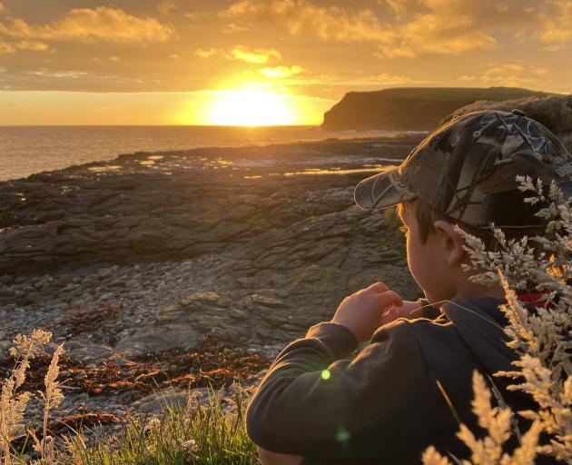 Hank Williams watches the last rays of sunshine disappear below the horizon at Curio Bay. PHOTO:...