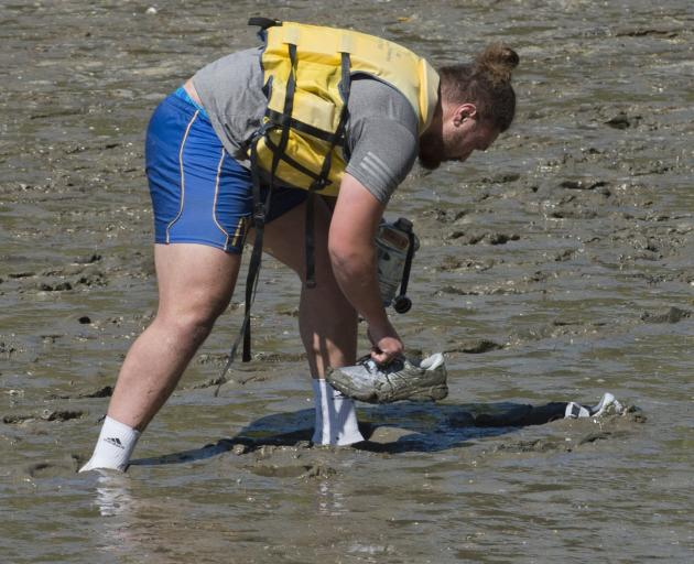 Prop Saula Mau gets his shoes out of the mud before embarking on the water at Careys Bay yesterday.
