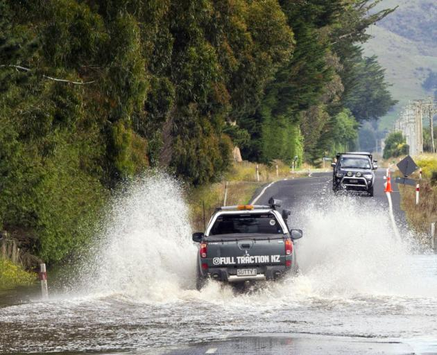 A vehicle cautiously crosses a water hazard on Allanton Rd yesterday. PHOTO: CHRISTINE O'CONNOR