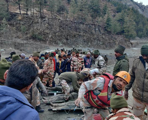 Members of Indo-Tibetan Border Police tend to people rescued after a Himalayan glacier broke and...