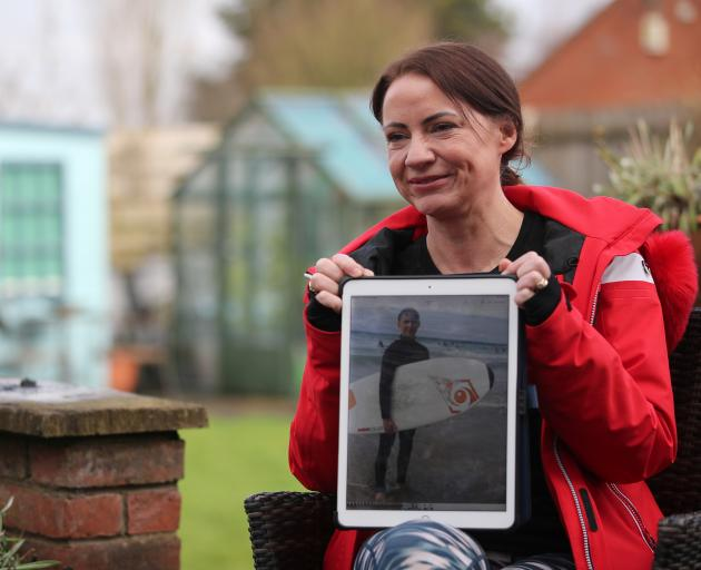 Sally Flavill shows a photograph of her nephew Joseph Flavill, who has awoken from a coma with no knowledge of the coronavirus disease (COVID-19) pandemic after he was injured in a car accident in March 2020. Photo: Reuters
