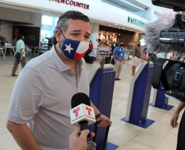 Ted Cruz answers questions from media after flying back to Texas. Photo: Reuters