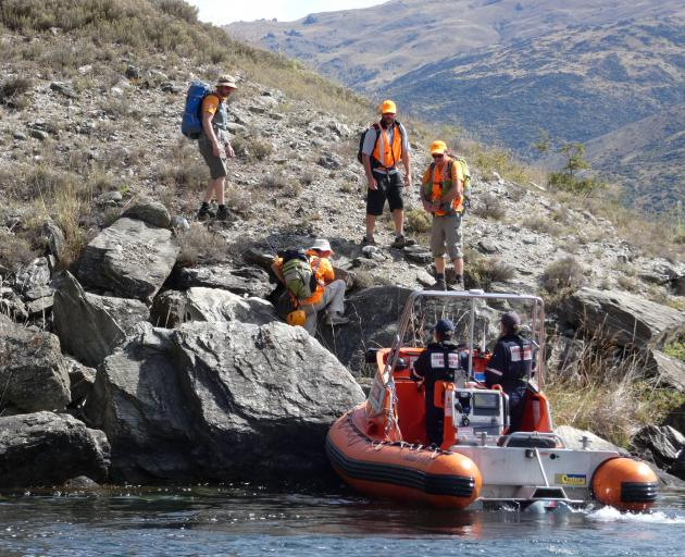 Central Otago Land Search and Rescue volunteers scramble down from the Lake Dunstan cycling and...