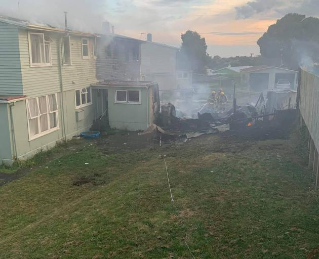 New Plymouth firefighters dampen down hotspots after a house fire this morning. Photo / Kayla Bridger
