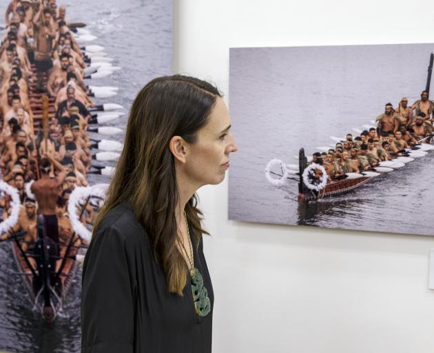 Prime Minister Jacinda Ardern inspects photographs of waka as she visits the He Kaupapa Waka...