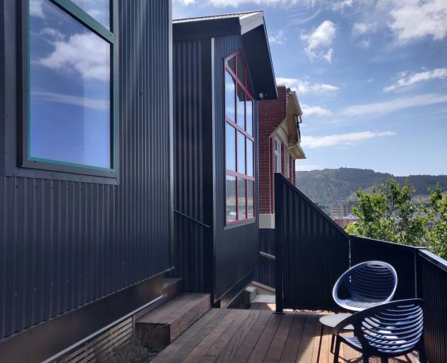 The homes' dark Colorsteel cladding is punctuated with red and green window frames.