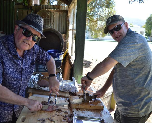 Residents of the ''Greek Quarter'' in Roslyn, Mark Caldwell (left) and Grant Harris carve the...