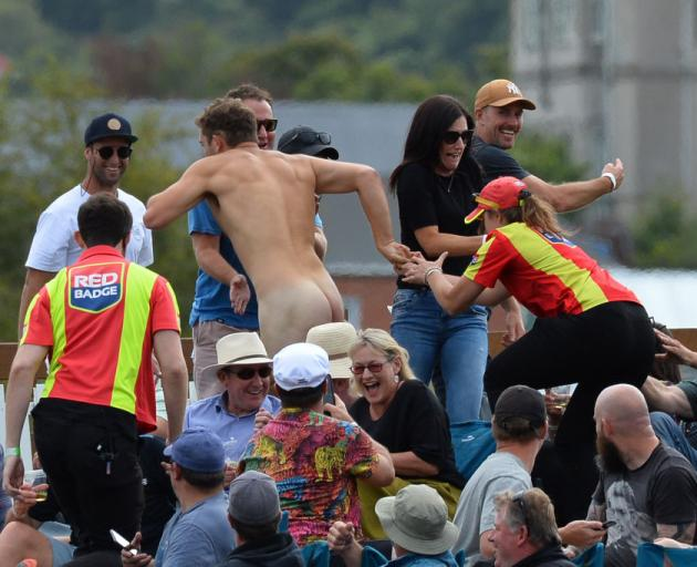Members of the ground security try to catch a streaker during the second Twenty20 international cricket match between New Zealand and Australia at University Oval in Dunedin. Photo: Getty Images
