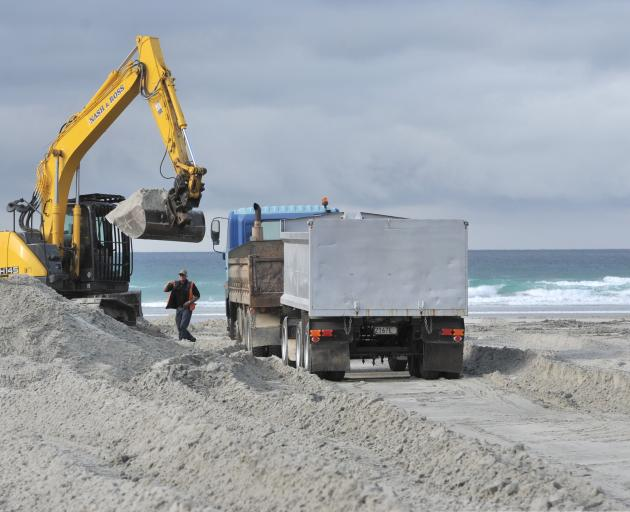 Contractors were criticised by beach-goers yesterday as they removed sand from Tomahawk Beach...