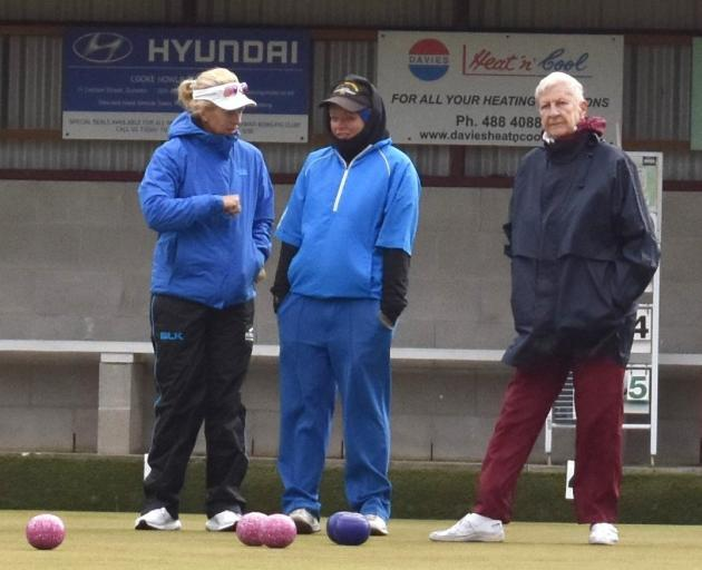 North East Valley pair Bronwyn Stevens (left) and Sarah Scott discuss options on the head as Tainui's Priscilla Holt (right) looks up the green at the bowl being delivered from playing partner Kathleen Harrington during the champion of champions women's p