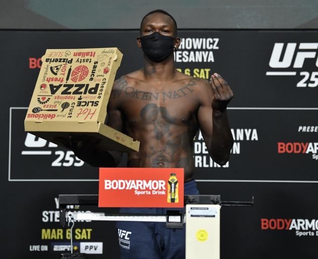 Israel Adesanya poses with a pizza box at the weigh-in for UFC 259. Photo: Getty Images