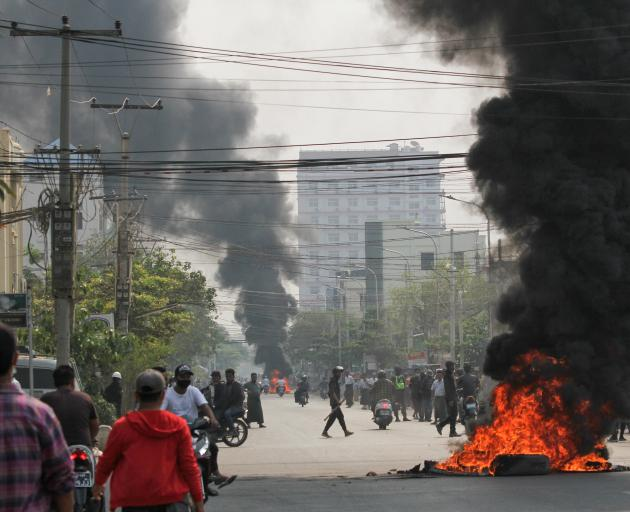 Tires burn on a street as protests against the military coup continue in Mandalay on Saturday....