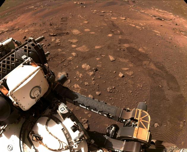 Wheel tread marks are left in the soil of Jezero Crater, as NASA rover Perseverance drives on...