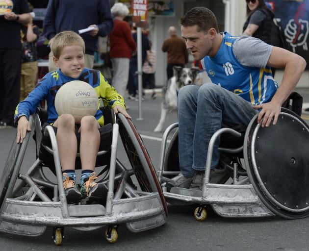 Otago wheelchair rugby captain Dillon Maydon shows Flynn Crossan (8), of Oamaru, the basics of...