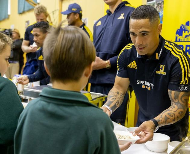 Highlander Aaron Smith hands a Green Island School pupil a bowl of oats at the school last week....