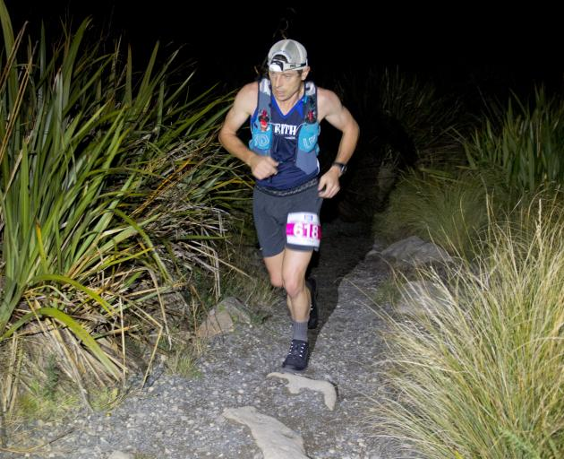 Chris Bisley runs through the dark on the way to winning the Three Peaks Plus One Mountain Race...