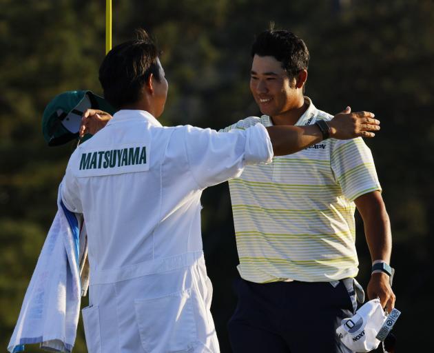 Japan's Hideki Matsuyama celebrates winning at Augusta with his caddie on the 18th green on...