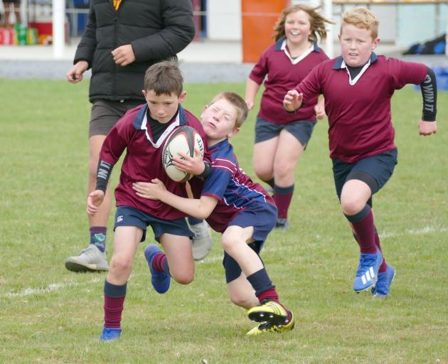 Henry Harwood (7) goes to tackle eventual try scorer Jake McHaffie (8) during an under-9s warm-up...