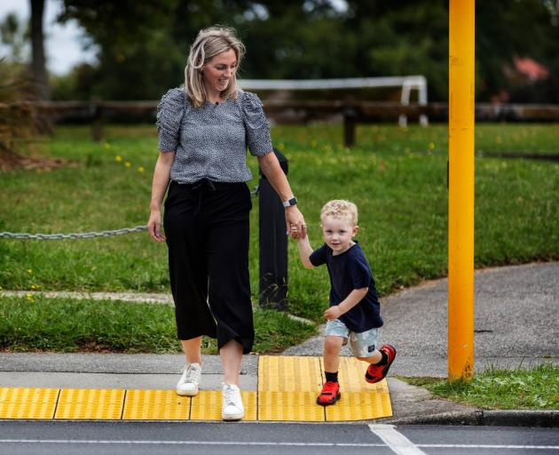 Bodie Hamilton about to cross at the signalled crossing near his home, with mum, Hayley. Despite the crash, Bodie doesn't have any fear about crossing there. Photo: Mike Scott