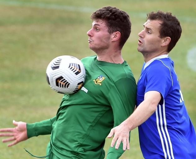 Green Island's Matt Brazier controls the ball on his chest as Mosgiel's Cam McPhaill defends...