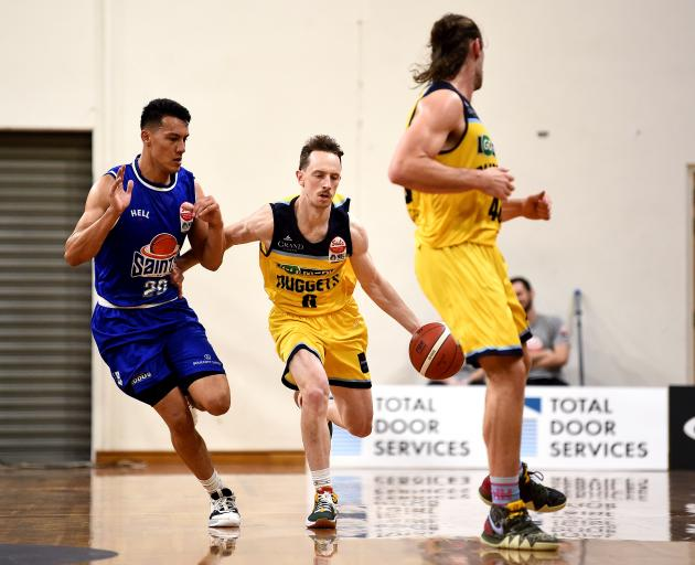 Otago Nuggets guard Darcy Knox dribbles the ball up court watched by Saints guard Kenneth Tuffin...