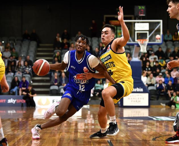 Saints guard Kerwin Roach drives to the basket while his opposite Richie Rodger tries to stop him...