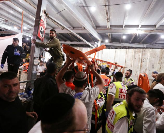 Medics and rescue workers carry stretchers at the Lag B'Omer event in Mount Mero on Friday. Photo...
