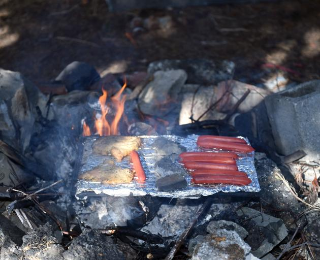 Some sausages and chicken schnitzel cook on the makeshift barbecue. PHOTO: GREGOR RICHARDSON