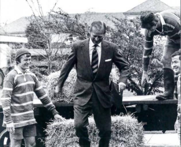 The Duke of Edinburgh, HRH Prince Philip, steps down from a tractor trailer, alongside Roy Day,...