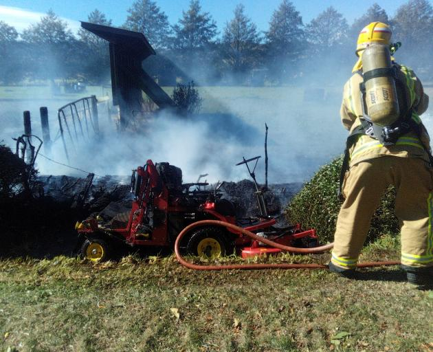 Firefighters attend a hedge fire in Guy Rd, Mosgiel, as hot temperatures and high winds kept Fire...
