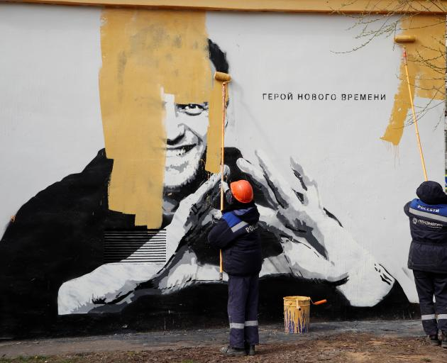 """Workers paint over a graffiti depicting Alexei Navalny in Saint Petersburg. The words say: """"The..."""