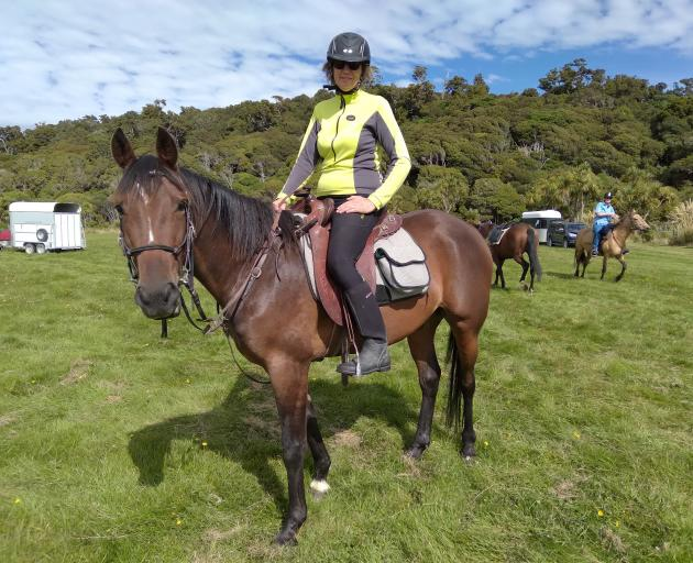 Long-time cavalcader and trail boss Jane Whitmore and her young horse Kenny near Kaka Point. Mrs...