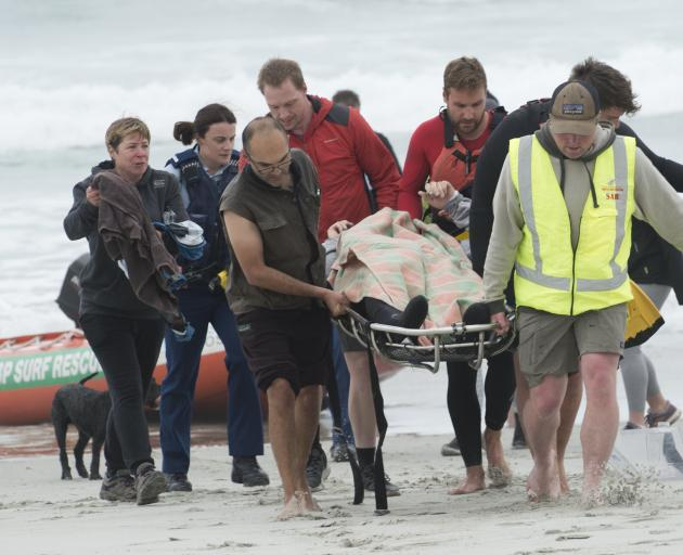 A hypothermic kayaker is taken by rescuers after being pulled from the surf at Ocean View on...