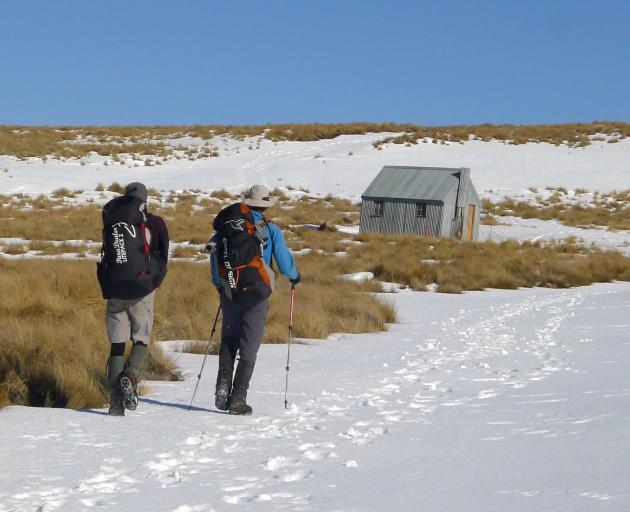 Two trampers make their way towards Wire Yards Hut in the Hawkdun Range, ...