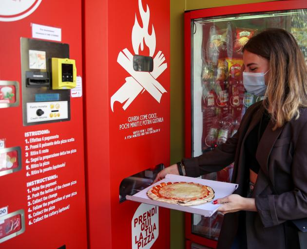 Fabrizia Pugliese collects her order at the first automatic pizza vending machine, which is capable of kneading, seasoning and cooking the pizza in three minutes. Photo: Reuters