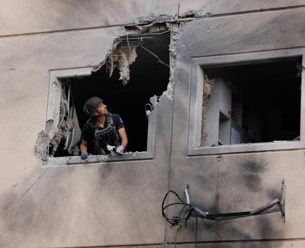An Israeli police bomb disposal expert looks out from the window of a residential building that...
