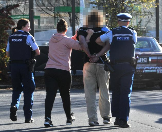 The accused is taken away by police following the incident at Countdown in central Dunedin...