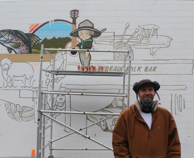 Artist Sean Duffell stands next to his mural that was commissioned under the Streets Alive...